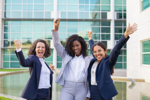 Three smiling businesswomen making winner gestures and rejoicing at corporate success