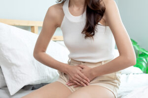 Woman sitting on her bed experiencing bladder pain